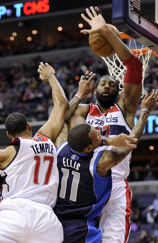 Dallas Mavericks guard Monta Ellis (11) goes to the basket against Washington Wizards forward Nene, top right, and Garrett Temple (17) during the first half of an NBA basketball game, Wednesday, Jan. 1, 2014, in Washington