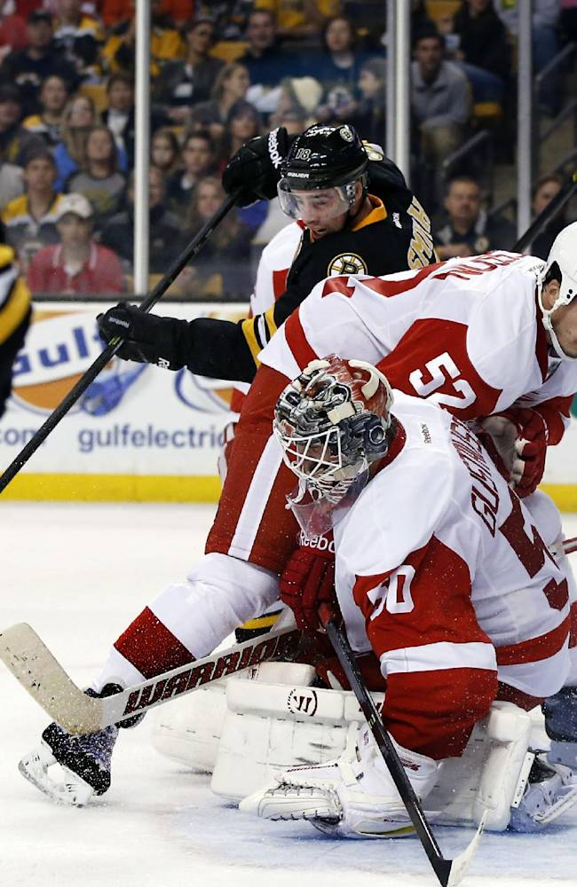 Detroit Red Wings goalie Jonas Gustavsson (50) and defenseman Jonathan Ericsson (52) protect the goal against Boston Bruins right wing Reilly Smith (18) who tries to get to the puck near the crease in the second period of an NHL hockey game in Boston, Monday, Oct. 14, 2013