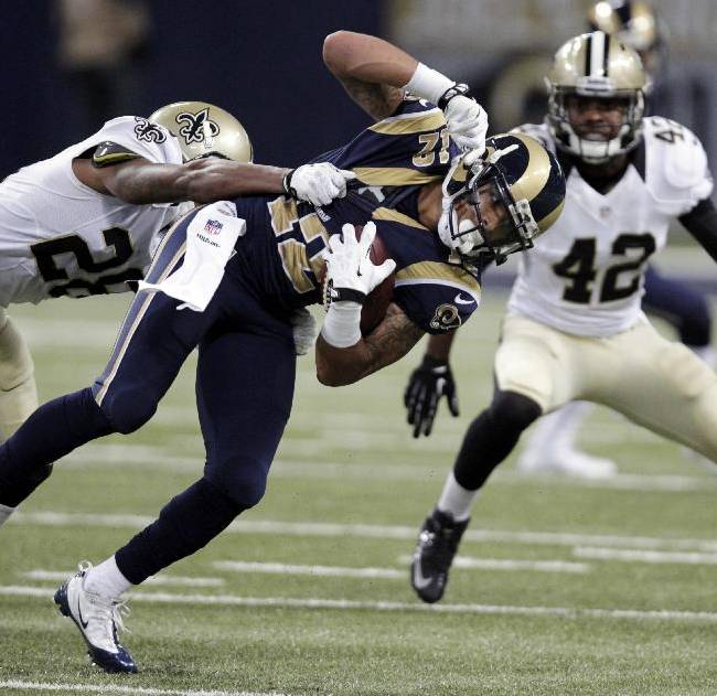 St. Louis Rams wide receiver Stedman Bailey, center, is pulled down by New Orleans Saints cornerback Keenan Lewis, left, as Saints safety Isa Abdul-Quddus is near after catching a pass for a 20-yard gain during the third quarter of an NFL football game Sunday, Dec. 15, 2013, in St. Louis