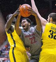 Washington State guard Royce Woolridge (22) breaks through the defense of Oregon forward Ben Carter (32) and forward Richard Amardi, left, during the first half of an NCAA college basketball game, Sunday, Jan. 26, 2014, in Pullman, Wash. (AP Photo/Dean Hare)