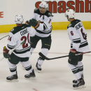 Minnesota Wild left wing Zach Parise, center, is congratulated after his empty-net goal by left wing Matt Cooke, left, and defenseman Christian Folin, of Sweden, against the Colorado Avalanche in the third period of the Wild's 3-0 victory in an NHL hockey