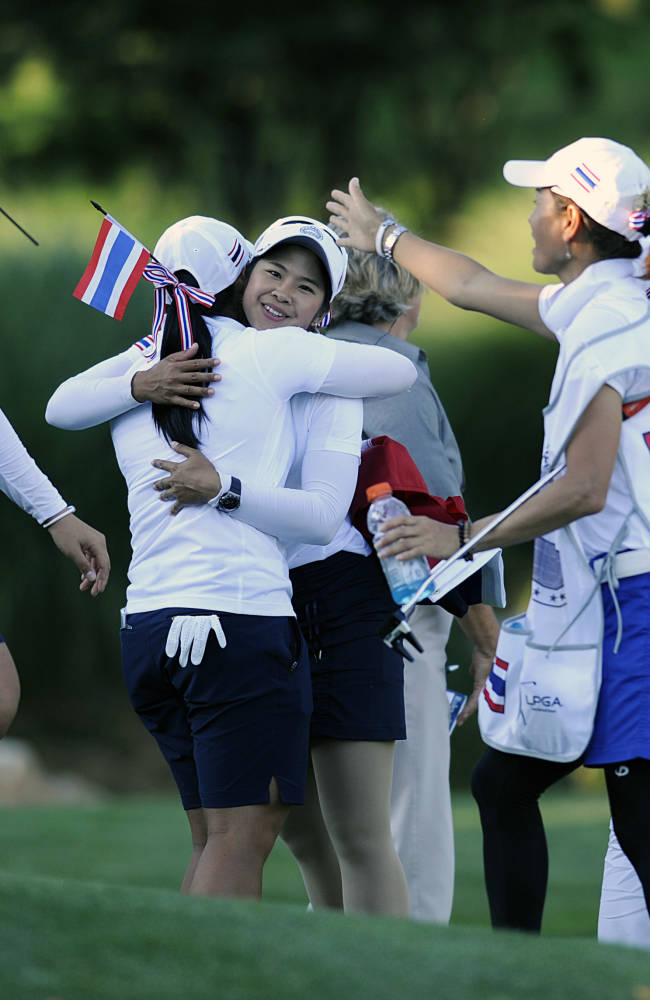 The Thailand team, including Pornanong Phatlum, center, celebrate after advancing to the final round of the International Crown golf tournament on Saturday, July 26, 2014, in Owings Mills, Md