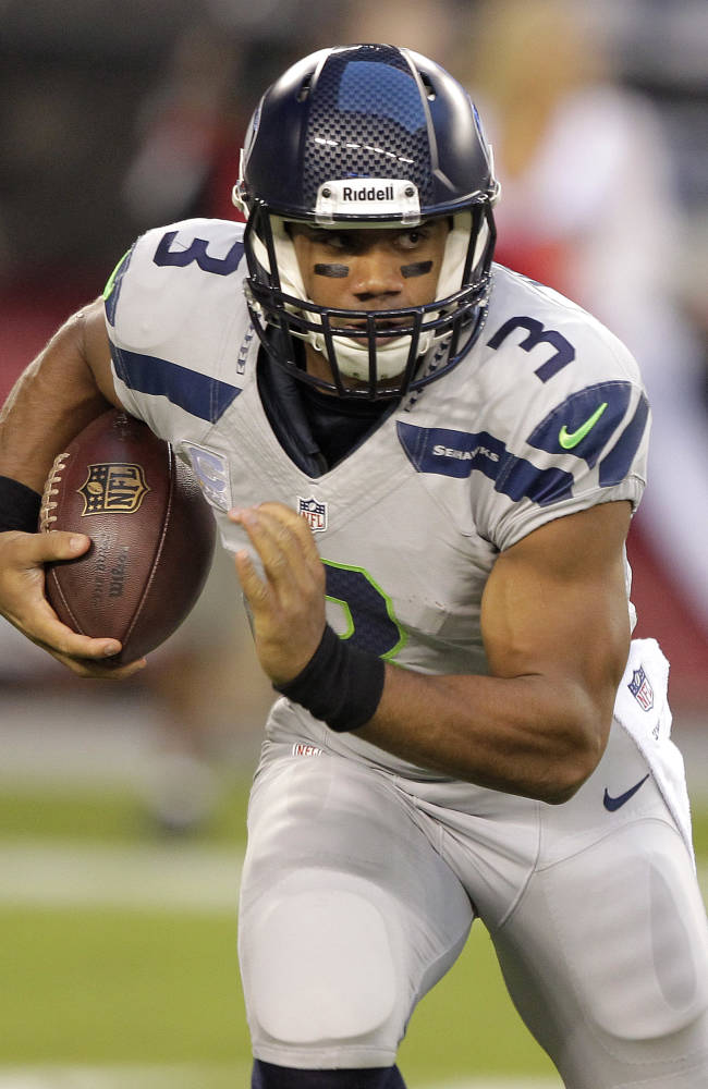 Seattle Seahawks quarterback Russell Wilson runs against the Arizona Cardinals during the first half of an NFL football game, Thursday, Oct. 17, 2013, in Glendale, Ariz