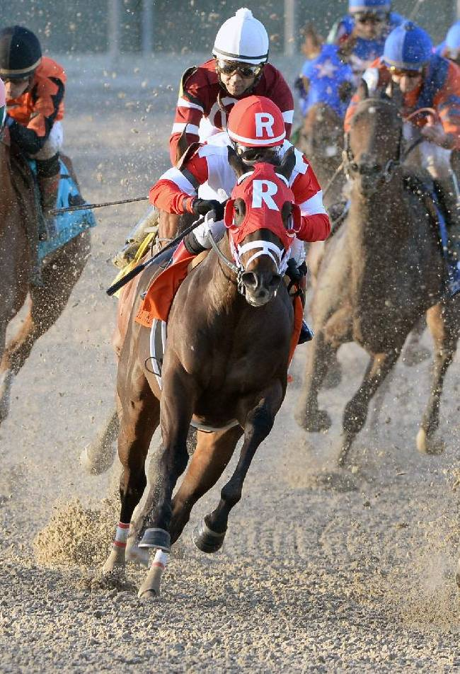 In a photo provided by Fair Grounds Race Course, Rosie Napravnik turns for home at the top of the stretch aboard Vicar's In Trouble, center, to win the Grade III Lecomte Stakes for 3 year olds at Fair Grounds Race Course on Saturday, Jan. 18, 2014, in New Orleans