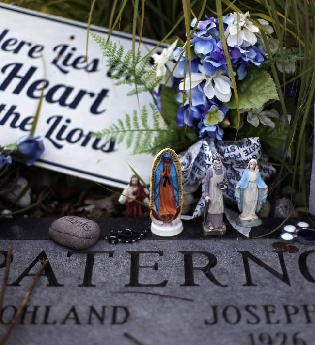 Mementos rest on the grave of former Penn State football coach Joe Paterno at Spring Creek Presbyterian Cemetery in State College, Pa., on the eve of Penn State's homecoming game against Northwestern, Friday, Sept. 26, 2014.