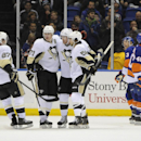 Pittsburgh Penguins' Sidney Crosby (87) skates in to celebrate James Neal's (18), third from left, with Evgeni Malkin (71) and Kris Letang (58) as New York Islanders' Travis Hamonic (3) and Michael Grabner (40) react in the second period of an NHL hockey