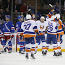 New York Islanders left wing Nikolay Kulemin (86) of Russia celebrates with teammates after scoring on New York Rangers goalie Henrik Lundqvist, far left, of Sweden, in the second period of an NHL hockey game at Madison Square Garden in New York, Tuesday