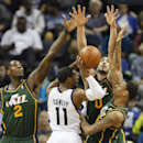 Memphis Grizzlies guard Mike Conley (11) tries to pass against Utah Jazz defenders Marvin Williams (2), Enes Kanter (0) and Diante Garrett (8) in the second half of an NBA basketball game on Wednesday, March 19, 2014, in Memphis, Tenn. The Grizzlies won 9