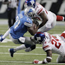 Detroit Lions running back Reggie Bush is tackled by New York Giants strong safety Stevie Brown (27) and cornerback Walter Thurmond (24) during the first quarter of an NFL football game in Detroit, Monday, Sept. 8, 2014 The Associated Press