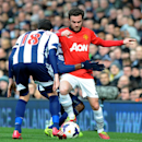 Manchester United's Juan Mata is held back by West Brom's Youssuf Mulumbu during the English Premier League soccer match between West Bromwich Albion and Manchester United at The Hawthorns Stadium in West Bromwich, England, Saturday, March 8, 2014