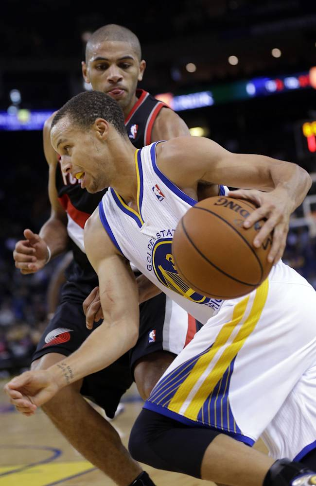 Golden State Warriors' Stephen Curry dribbles next to Portland Trail Blazers' Nicolas Batum during the second half of an NBA preseason basketball game on Thursday, Oct. 24, 2013, in Oakland, Calif
