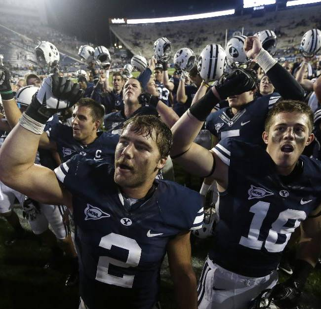 In this Sept. 7, 2013, file photo, Brigham Young's Spencer Hadley (2) and DJ Doman (18) celebrate with other players following their NCAA college football game against Texas, in Provo, Utah. Hadley, a suspended BYU football player, says he violated the school's honor code by drinking alcohol and partying in Las Vegas. Sports Illustrated reports Wednesday that the 23-year-old is ashamed of his actions. The senior linebacker from Connell, Wash., missed last weekend's game against rival Utah and can't rejoin the team until the Cougars play Boise State on Oct. 25 at the earliest