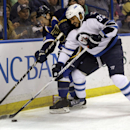 St. Louis Blues' Kevin Shattenkirk, left, and Winnipeg Jets' Dustin Byfuglien chase after a loose puck during the first period of an NHL hockey game Monday, March 17, 2014, in St. Louis The Associated Press