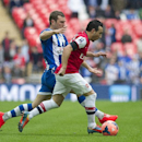 Arsenal's Santi Cazorla, right, fights for the ball with Wigan Athletic's James McArthur during their English FA Cup semifinal soccer match, at the Wembley Stadium in London, Saturday, April 12, 2014
