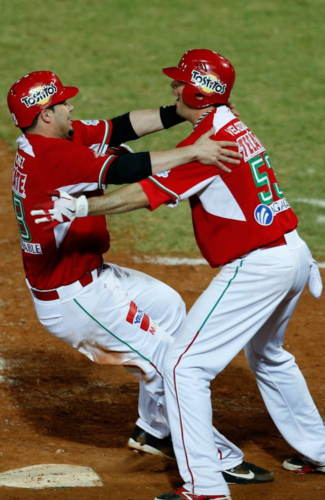 Mexico infielder Yunesky Sanchez, left, celebrates with his teammate Gil Velazquez after Sanchez scored the winning run against the Dominican Republic in their Caribbean Series baseball semifinal game in Porlamar, Venezuela, Thursday, Feb. 6, 2014. Mexico won the game 3-2, advancing to the final