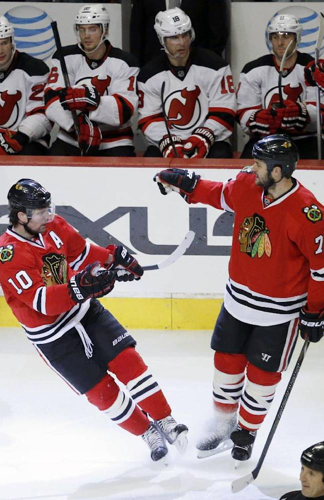 Chicago Blackhawks left wing Patrick Sharp, left, celebrates his second goal with Brent Seabrook (7) during the third period of an NHL hockey game against the New Jersey Devils, Monday, Dec. 23, 2013, in Chicago. The Blackhawks won 5-2