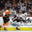Chicago Blackhawks' Daniel Carcillo (13), a former Philadelphia Flyers' player, stumbles after a hit from Philadelphia's Michael Del Zotto (15) during the first period of an NHL hockey game, Wednesday, March 25, 2015, in Philadelphia. (AP Photo/Matt Slocum)