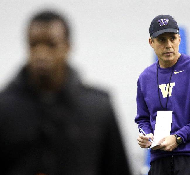 New Washington head football coach Chris Petersen, right, takes notes on the first day of spring NCAA college football practice, Tuesday, March 4, 2014, in Seattle