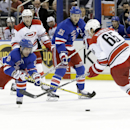 New York Rangers' Martin St. Louis (26) fights for control of the puck with Carolina Hurricanes' Ron Hainsey (65) during the second period of an NHL hockey game Tuesday, April 8, 2014, in New York The Associated Press