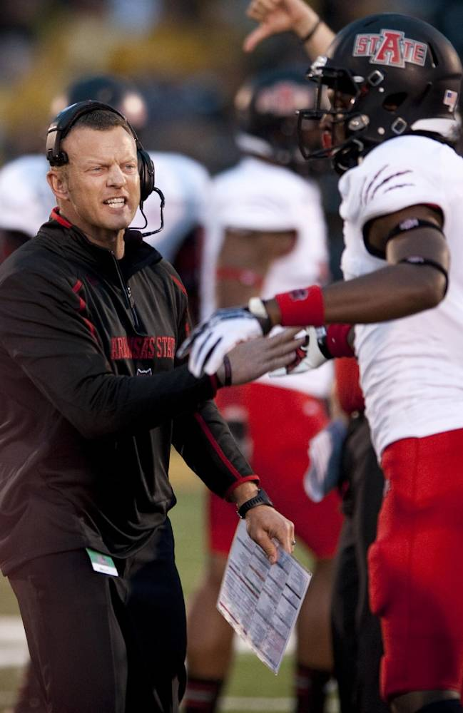 In this Sept. 28, 2013 file photo, Arkansas State head coach Bryan Harsin, left, encourages his player Phillip Butterfield, right, during the second quarter of an NCAA college football game against Missouri in Columbia, Mo. A person familiar with the decision tells The Associated Press that Boise State has hired  Harsin as its next coach. The person spoke on condition of anonymity because the move had not become official