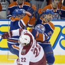 Arizona Coyotes Brandon McMillan (22) is hit by Edmonton Oilers Andrew Ference (21) and Boyd Gordon (27) during first period NHL hockey action in Edmonton, Alberta, on Sunday, Nov. 16, 2014 The Associated Press