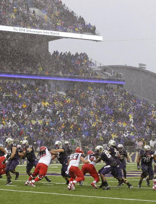 Heavy rain falls during a loose-ball situation on a Washington possession against Arizona in the first half of an NCAA college football game, Saturday, Sept. 28, 2013, in Seattle. Washington recovered the ball