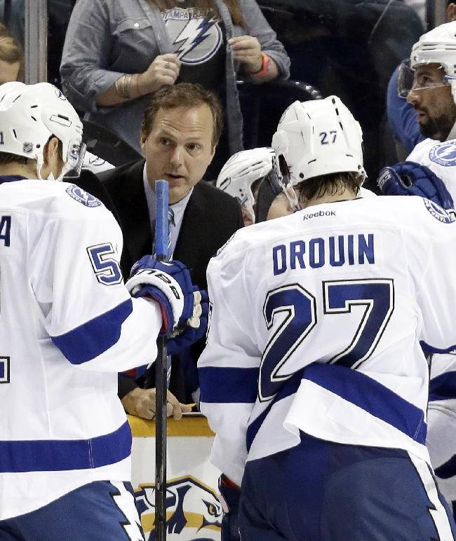 Tampa Bay Lightning head coach Jon Cooper, center, talks with his players during a timeout in the third period of a preseason NHL hockey game against the Nashville Predators on Tuesday, Sept. 24, 2013, in Nashville, Tenn. The Predators won 2-1