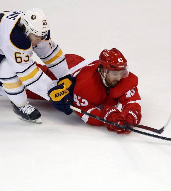 Detroit Red Wings' Darren Helm (43) knocks the puck away to stop a skate on goal by Buffalo Sabres' Tyler Ennis (63) during the third period of an NHL hockey game Friday, April 4, 2014, in Detroit. The Red Wings defeated the Sabres 3-2