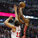 Miami Heat center Chris Bosh, right, shoots over Chicago Bulls center Joakim Noah, left, during the first half of an NBA basketball game in Chicago, Thursday, Dec. 5, 2013 The Associated Press