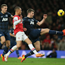Arsenal's Kieran Gibbs, centre, challenges Manchester United's Michael Carrick, right during their English Premier League soccer match between Arsenal and Manchester United at the Emirates stadium in London, Wednesday, Feb. 12, 2014