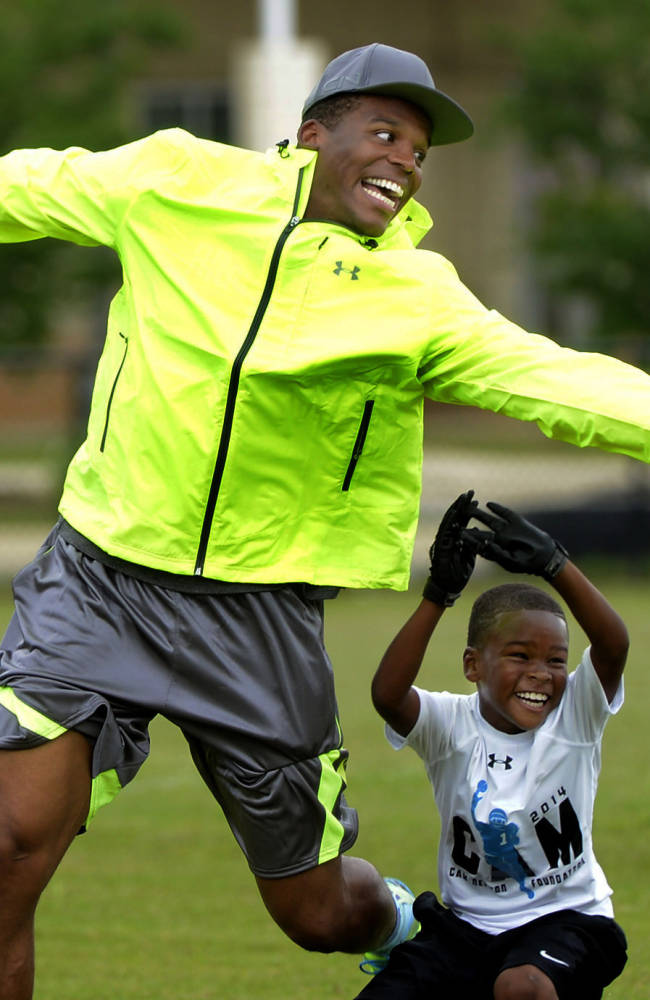 Carolina Panthers quarterback Cam Newton reaches to catch a pass over nine-year-old Ethan Nation during a break in his high school 7-on-7 football camp in Birmingham, Ala., Friday, June 13, 2014