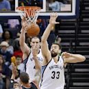 Portland Trail Blazers guard Damian Lillard (0) tries to put a shot over the reach of Memphis Grizzlies defenders Marc Gasol (33), of Spain, and Kosta Koufos in the second half of an NBA basketball game on Tuesday, March 11, 2014, in Memphis, Tenn. The Gr