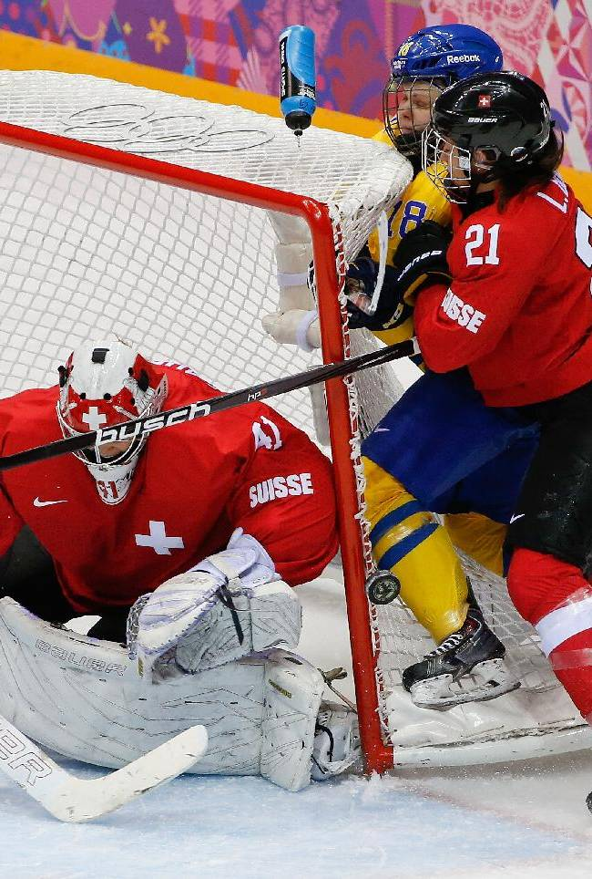 Laura Benz of Switzerland (21) pins Anna Borgqvist of Sweden (18) against the net as goalkeeper Florence Schelling of Switzerland (41) looks for the puck during the third period of the women's bronze medal ice hockey game at the 2014 Winter Olympics, Thursday, Feb. 20, 2014, in Sochi, Russia