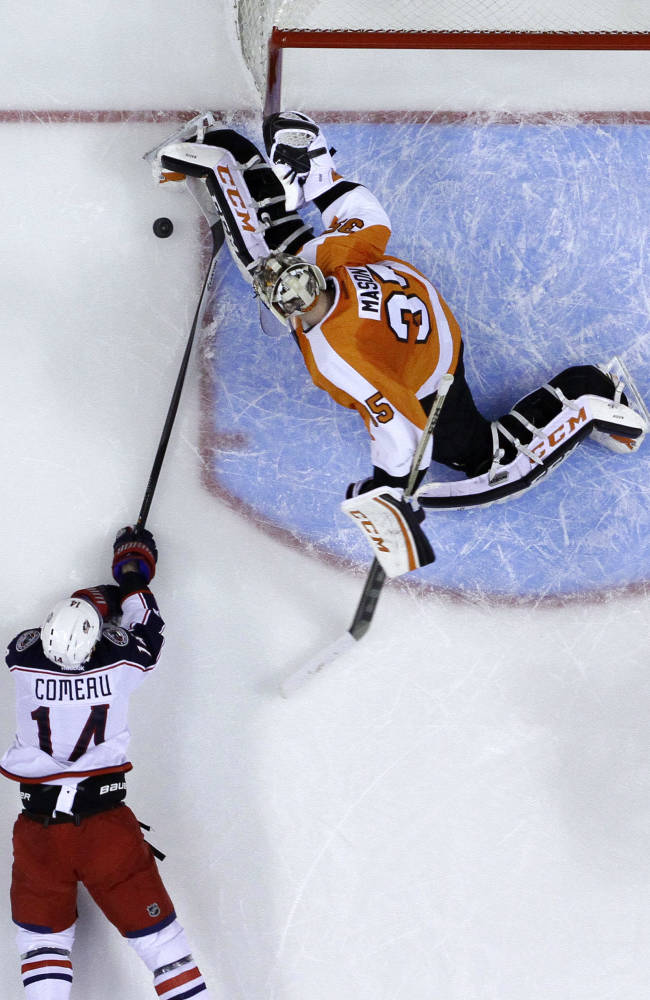 Columbus Blue Jackets' Blake Comeau, left, tries to get a shot past Philadelphia Flyers goalie Steve Mason during the first period of an NHL hockey game, Thursday, April 3, 2014, in Philadelphia
