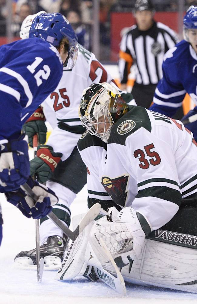 Minnesota Wild goalie Darcy Kuemper searches for the puck between Toronto Maple Leafs' Mason Raymond (12) and Joffrey Lupul (19) during the second period of an NHL hockey game in Toronto on Tuesday, Oct. 15, 2013
