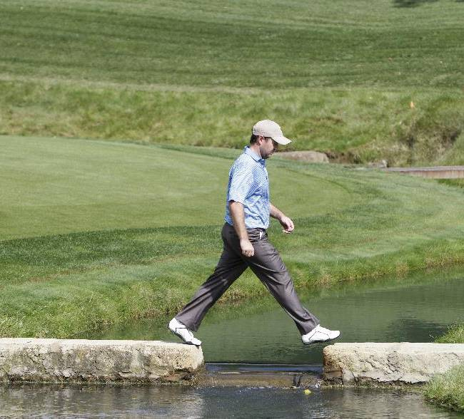 International team player Richard Sterne, of South Africa, steps over a creek as he walks up to the 14th green during a practice round for the Presidents Cup golf tournament at Muirfield Village Golf Club Wednesday, Oct. 2, 2013, in Dublin, Ohio