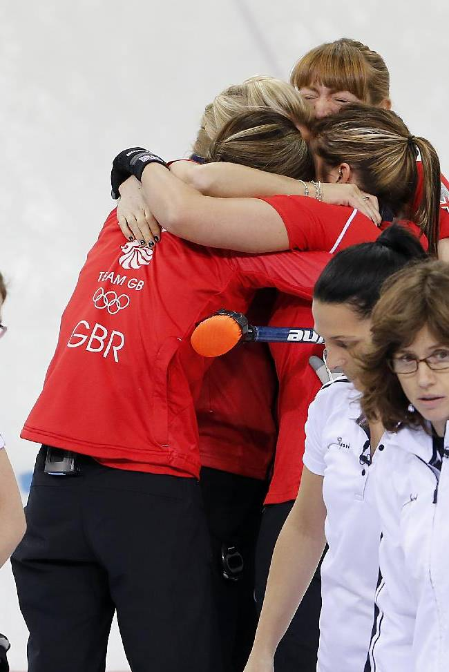 Britain's women's curling team embrace each other as they celebrate after beating Switzerland in the women's curling bronze medal game at the 2014 Winter Olympics, Thursday, Feb. 20, 2014, in Sochi, Russia. Seen in the foreground from left to right, is  Switzerland's Carmen Kueng, Janine Greiner, Carmen Schaefer and skip Mijam Ott