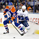 Vancouver Canucks' Chris Higgins (20) chases Edmonton Oilers' Martin Marincin (85) during first-period NHL hockey game action in Edmonton, Alberta, Friday, Oct. 17, 2014 The Associated Press