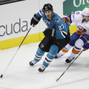 San Jose Sharks' Scott Hannan (27) is chased by New York Islanders' Cal Clutterbuck (15) during the first period of an NHL hockey game Saturday, Nov. 1, 2014, in San Jose, Calif The Associated Press