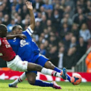 Arsenal's Yaya Sanogo, fights for the ball with Everton's Sylvain Distin, during their FA Cup quarterfinal soccer match, at Emirates Stadium, in London, Saturday, March 8, 2014