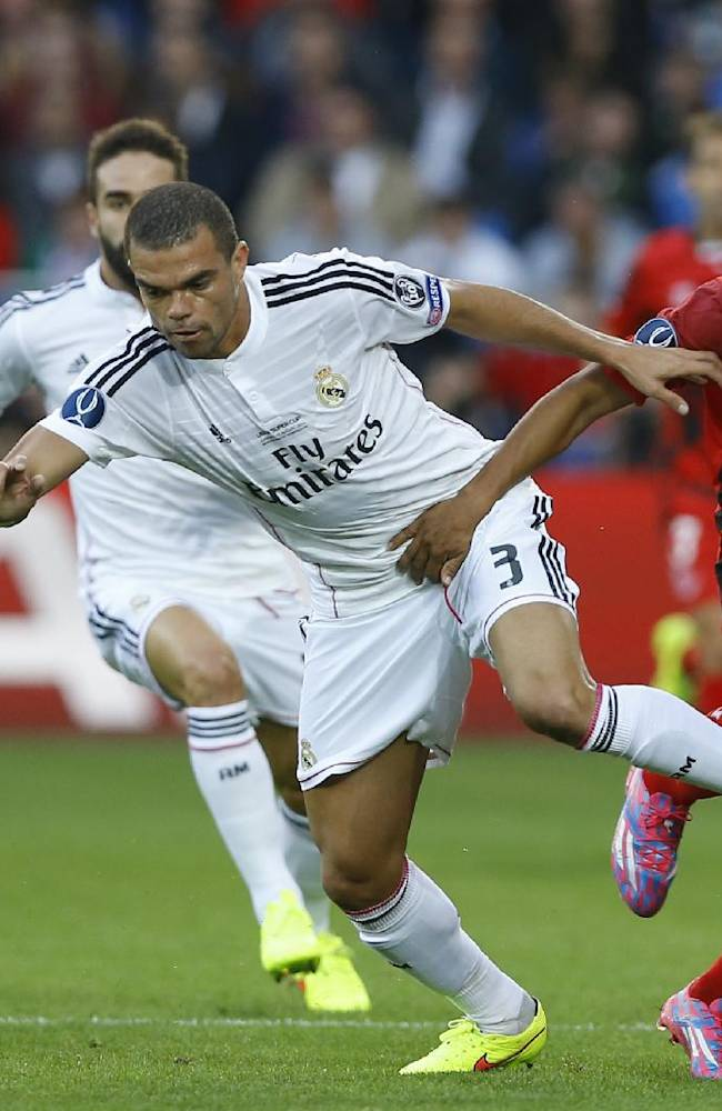 Real Madrid's Pepe, left holds off Sevilla's Carlos Bacca during the UEFA Super Cup soccer match between Read Madrid and Sevilla at Cardiff City Stadium in Wales Tuesday, Aug. 12, 2014