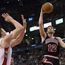 Chicago Bulls' Kirk Hinrich (12) scores on Toronto Raptors' Tyler Hansbrough during the second half of an NBA basketball game, Wednesday, Feb. 19, 2014 in Toronto The Associated Press