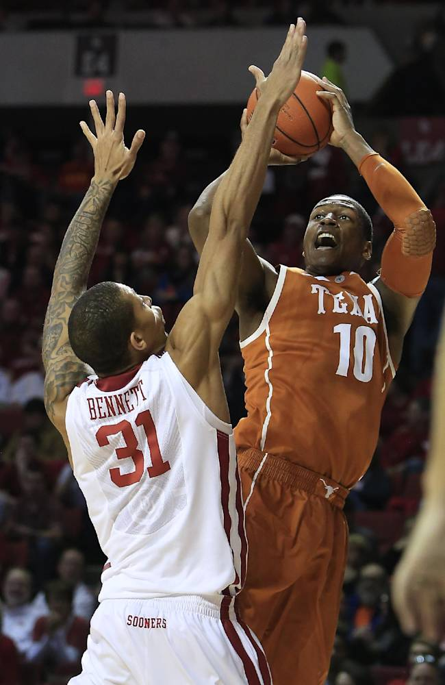 Texas forward Jonathan Holmes (10) shoots over Oklahoma forward D.J. Bennett (31) during the first half of an NCAA college basketball game in Norman, Okla., Saturday, March 1, 2014