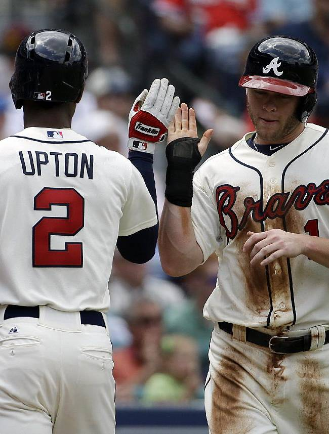 Atlanta Braves' Tyler Pastornicky, right, high-fives teammate B.J. Upton after scoring off a double by Jason Heyward in the second inning of a baseball game against the Washington Nationals, Sunday, April 13, 2014, in Atlanta