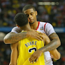 Louisville forward Chane Behanan give Michigan guard Trey Burke a hug after defeating Michigan to win the NCAA Division I National Championship on Monday, April 8, 2013, in Atlanta. Louisville beat Michigan 82-76 for NCAA title. (AP Photo/Atlanta Journal Constitution, Curtis Compton)