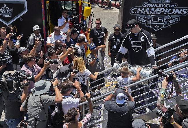 CORRECTS SONS NAME TO MASON-Los Angeles Kings' Dustin Brown, right, and his son Mason, carry the NHL hockey Stanley Cup down off the parade truck after a parade, Monday, June 16, 2014, in Los Angeles. The parade and rally were held to celebrate the Kings' second Stanley Cup championship in three seasons. The Kings defeated the New York Rangers for the title