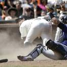 Colorado Rockies catcher Yorvit Torrealba, foreground, shows home plate umpire Alfonso Marquez the ball after tagging out San Francisco Giants' Brandon Belt, left, at home during the seventh inning of a baseball game in San Francisco, Saturday, May 25, 2013. (AP Photo/Jeff Chiu)