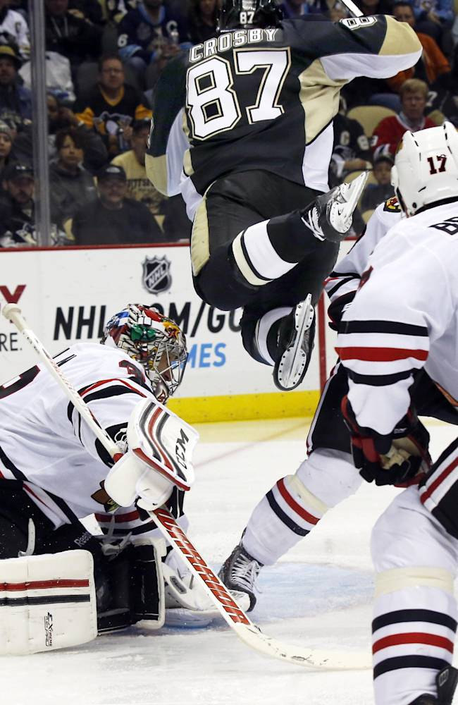 Pittsburgh Penguins' Sidney Crosby (87) leaps through the goal crease in front of Chicago Blackhawks goalie Nikolai Khabibulin (39), of Russia, in the second period of an NHL preseason hockey game on Monday, Sept. 23, 2013, in Pittsburgh