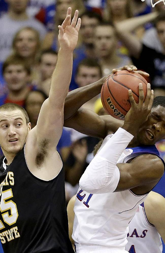 Kansas' Joel Embiid beats Fort Hays State's Marty Wendel to a rebound during the first half of an exhibition NCAA college basketball game Tuesday, Nov. 5, 2013, in Lawrence, Kan