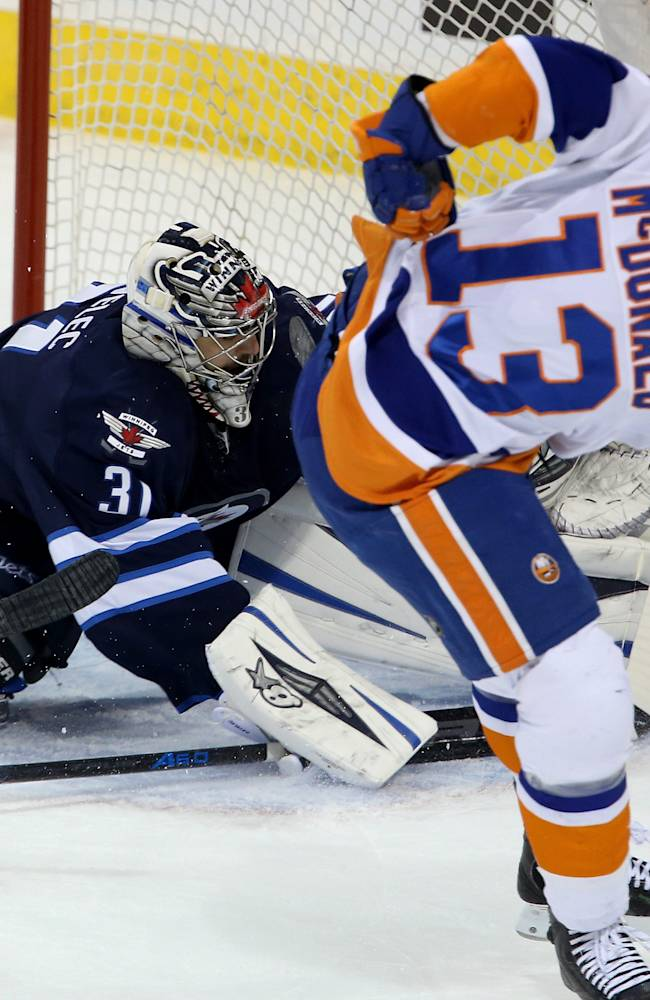 New York Islanders' Colin McDonald (13) squeezes the puck between Winnipeg Jets goaltender Ondrej Pavelec (31) and the post for a goal during the first period of an NHL hockey game in Winnipeg, Manitoba, Tuesday, March 4, 2014